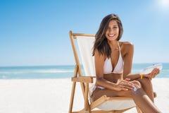 Woman applying sunscreen Stock Photos