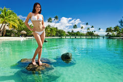 Young woman in white bikini standing on beach royalty free stock photography