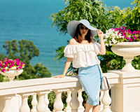 Young woman in a white blouse, blue pencil skirt and hat on a ba Stock Photography