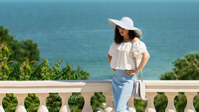 Young woman in a white blouse, blue pencil skirt and hat on a ba Royalty Free Stock Photography