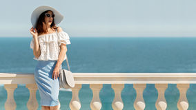 Young woman in a white blouse, blue pencil skirt and hat on a ba Stock Photo