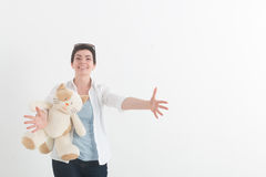 Young woman in a white blouse with cat is preparing to hug someone, spreading her hands wide apart and greeting smiling Royalty Free Stock Photography