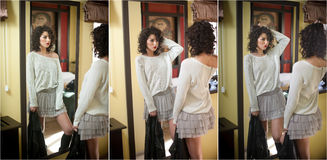 Young woman in white blouse and gray short tutu skirt looking into large mirror holding black leather jacket. Beautiful brunette. Young woman in white blouse and royalty free stock photography