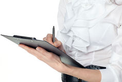 Young woman in white blouse writing on a clipboard Stock Photography