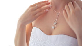 Young woman in white bridal dress wearing shiny diamond pendant stock video