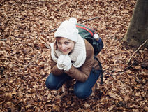 Young woman in white cap squats in the brown leaves at the fores Stock Photography