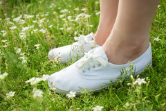 Young woman in white classic sneakers standing in grass on spring meadow Stock Images