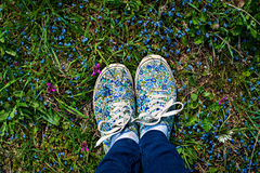 Young woman in white classic sneakers standing in grass on spring meadow with flowers. Legs close-up. royalty free stock photos