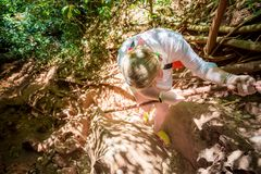 Young woman in white climbs the mountain on a rope. View from above. Tropical jungle. She is looking down royalty free stock photography