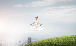 Young woman keeping mind conscious. Young woman in white clothing keeping eyes closed and looking concentrated while meditating on cloud in the air with city Royalty Free Stock Images
