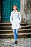 Young woman in a white coat walking through the old Lviv Stock Images