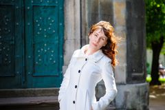 Young woman in a white coat walking through the old Lviv Royalty Free Stock Images