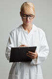 Young woman with white coat writes on a clipboard Royalty Free Stock Photos