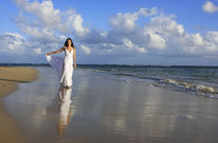 Young woman in white dress on a beach Stock Photos