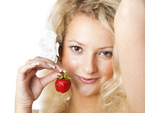 Young woman in white dress eating strawberries. Isolated on white background Stock Images