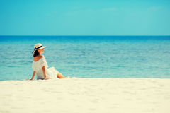 Young woman in white dress and hat lying on sand of tropical beach having great summer time Stock Photos
