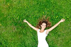 Young woman in white dress lying on grass Stock Image