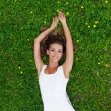 Young woman in white dress lying on grass Royalty Free Stock Images