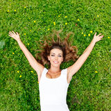 Young woman in white dress lying on grass Royalty Free Stock Photos