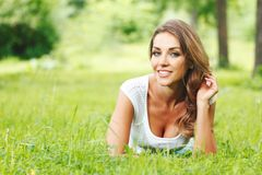 young woman in white dress lying on grass Royalty Free Stock Image