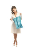 A young woman in a white dress opening a bag Royalty Free Stock Images
