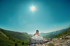 Young woman in white dress playing flute sitting on a mountain r. Ock. Travelling concept art photo Royalty Free Stock Photos