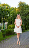Young woman in white dress posing standing in a park Royalty Free Stock Image