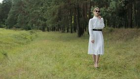 Young woman in white dress posing, walking on grass with black glasses. Slow motion stock footage