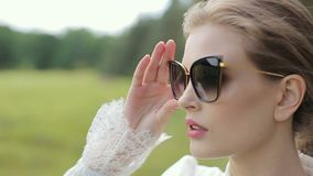 Young woman in white dress posing, walking on grass with black glasses. Slow motion stock video footage