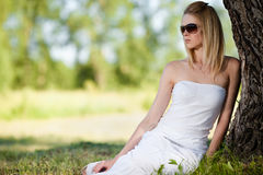 Young woman in white dress relaxing in the park Royalty Free Stock Images