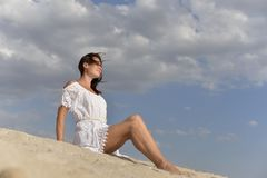 A young woman in a white dress sitting barefoot on the sandy beach. stock photography