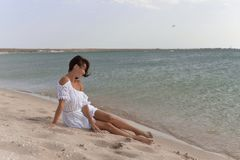 A young woman in a white dress sitting barefoot on the sandy beach. royalty free stock photo