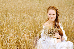 Young woman in white dress sitting in field with wheat Royalty Free Stock Image