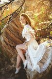Young woman in white dress is sitting on the stone under the branches Royalty Free Stock Photo