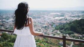 Young woman in white dress standing on balcony of villa looking at city. Young brunette woman in white dress standing on balcony of villa looking at city on hot stock footage