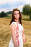 Young woman in white dress standing in a fresh mown corn field Stock Photos