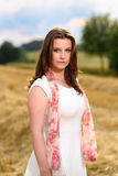 Young woman in white dress standing in a fresh mown corn field Royalty Free Stock Photo