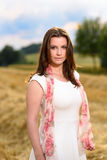 Young woman in white dress standing in a fresh mown corn field Stock Image