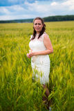 Young woman in white dress standing in rye field Royalty Free Stock Photo