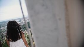 Young woman in white dress standing on stairs of villa looking at city. Young brunette woman in white dress standing on stairs of villa looking at city on hot stock video