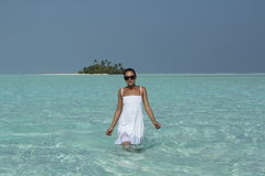 Young woman in a white dress standing in turquise water Maldives Stock Photos