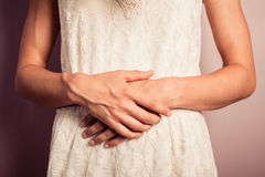 Young woman in white dress with stomach pains. A young woman wearing a white dress has stomach pains Royalty Free Stock Images