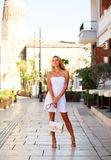 Young woman in white dress on street of summer tourist city Stock Image