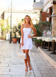 Young woman in white dress on street of summer tourist city Royalty Free Stock Images