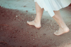 Young woman in white dress walking alone on the beach Royalty Free Stock Image