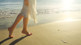 Young woman in white dress walking alone on sandy beach at sunri Stock Photo