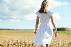 Young woman in white dress walking along on field Royalty Free Stock Photos