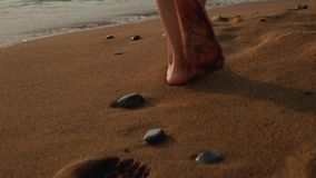Young woman in white dress walking barefoot on beach leaving footprints wet sand stock video