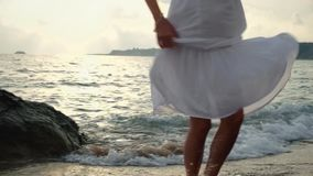 Young woman in white dress walking on beach stock video footage