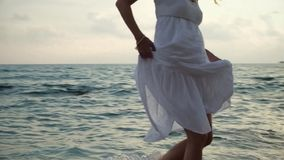 Young woman in white dress walking on beach stock footage